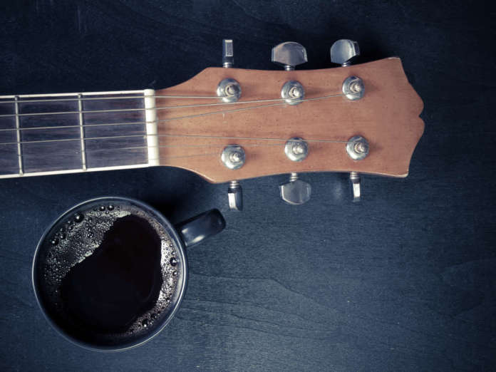 Coffee and guitar on wooden table. (Vintage Style)